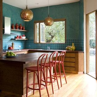 メルボルンの大きいトランジショナルスタイルのおしゃれなキッチン (フラットパネル扉のキャビネット、中間色木目調キャビネット、青いキッチンパネル、アンダーカウンターシンク、木材カウンター、セラミックタイルのキッチンパネル、シルバーの調理設備の、淡色無垢フローリング) の写真