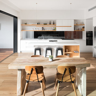 Contemporary eat-in kitchen in Melbourne with a double-bowl sink, flat-panel cabinets, white cabinets, black splashback, glass sheet splashback, stainless steel appliances, light hardwood floors, with island and beige floor.