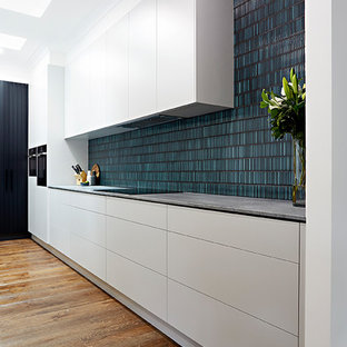 Design ideas for a single-wall kitchen pantry in Melbourne with a built-in sink, beaded cabinets, white cabinets, marble worktops, metro tiled splashback, black appliances, plywood flooring and an island.