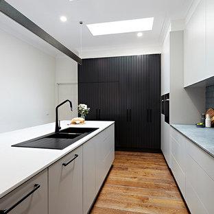 Exempel på ett linjärt skafferi, med en nedsänkt diskho, luckor med profilerade fronter, vita skåp, marmorbänkskiva, stänkskydd i tunnelbanekakel, svarta vitvaror, plywoodgolv och en köksö