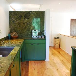 Modelo de cocina moderna, grande, cerrada, con fregadero bajoencimera, armarios con paneles lisos, puertas de armario verdes, encimera de ónix, salpicadero gris, salpicadero de vidrio, electrodomésticos de colores, suelo de madera clara, una isla y suelo beige