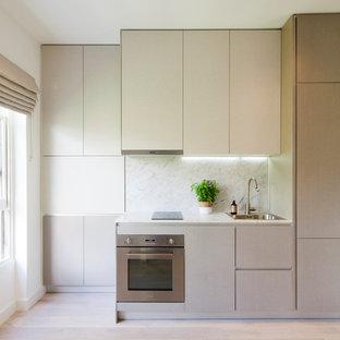 Idee per una piccola cucina lineare minimal con lavello a vasca singola, ante lisce, ante grigie, top in marmo, paraspruzzi in lastra di pietra, elettrodomestici in acciaio inossidabile e parquet chiaro