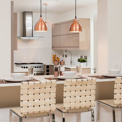 Inspiration for a contemporary u-shaped eat-in kitchen remodel in Dublin with flat-panel cabinets, brown cabinets, white backsplash, subway tile backsplash, stainless steel appliances and an island