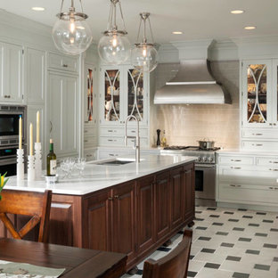 Inspiration for a large transitional u-shaped eat-in kitchen in Houston with a single-bowl sink, glass-front cabinets, white cabinets, grey splashback, ceramic splashback, stainless steel appliances, ceramic floors and with island.