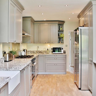 Photo of a medium sized classic l-shaped kitchen in London with a belfast sink, recessed-panel cabinets, grey cabinets, stainless steel appliances, a breakfast bar and beige floors.