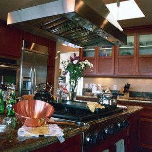 オレンジカウンティの広いトラディショナルスタイルのおしゃれなキッチン (ドロップインシンク、シェーカースタイル扉のキャビネット、赤いキャビネット、御影石カウンター、緑のキッチンパネル、シルバーの調理設備、無垢フローリング、赤い床、緑のキッチンカウンター) の写真