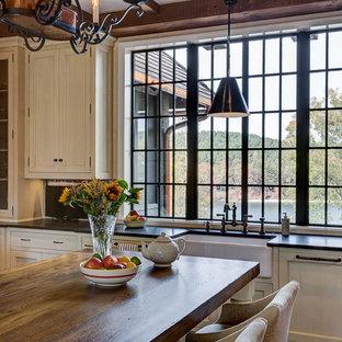 他の地域の広いカントリー風おしゃれなキッチン (エプロンフロントシンク、シェーカースタイル扉のキャビネット、白いキャビネット、人工大理石カウンター、赤いキッチンパネル、レンガのキッチンパネル、パネルと同色の調理設備、濃色無垢フローリング) の写真