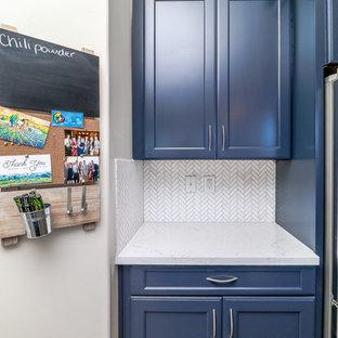 Offene, Mittelgroße Moderne Küche in L-Form mit Unterbauwaschbecken, Schrankfronten mit vertiefter Füllung, blauen Schränken, Quarzwerkstein-Arbeitsplatte, Küchenrückwand in Weiß, Küchengeräten aus Edelstahl, Porzellan-Bodenfliesen, Kücheninsel, braunem Boden, weißer Arbeitsplatte und Rückwand aus Marmor in Las Vegas