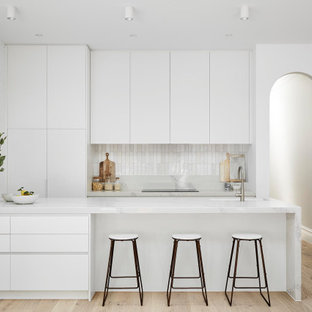 This is an example of a modern galley kitchen in Melbourne with an undermount sink, flat-panel cabinets, white cabinets, white splashback, panelled appliances, medium hardwood floors, a peninsula, brown floor and white benchtop.