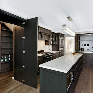 Midcentury galley open plan kitchen in Central Coast with a single-bowl sink, glass-front cabinets, dark wood cabinets, quartzite benchtops, white splashback, stone slab splashback, black appliances, vinyl floors and with island.