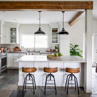 サンディエゴの中くらいのトランジショナルスタイルのおしゃれなキッチン (エプロンフロントシンク、シェーカースタイル扉のキャビネット、珪岩カウンター、シルバーの調理設備、グレーのキッチンカウンター、白いキャビネット、白いキッチンパネル、スレートの床、グレーの床) の写真