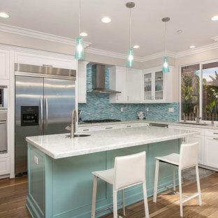 Inspiration för stora maritima turkost kök, med en enkel diskho, luckor med infälld panel, vita skåp, bänkskiva i kvartsit, blått stänkskydd, stänkskydd i glaskakel, rostfria vitvaror, mellanmörkt trägolv, en köksö och brunt golv