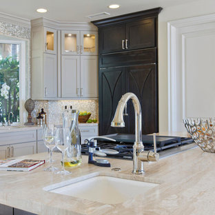 Mid-sized transitional l-shaped open plan kitchen in San Diego with an undermount sink, recessed-panel cabinets, beige cabinets, limestone benchtops, beige splashback, glass tile splashback, stainless steel appliances, travertine floors and with island.