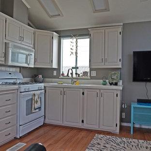 サンディエゴの小さいコンテンポラリースタイルのおしゃれなキッチン (アンダーカウンターシンク、レイズドパネル扉のキャビネット、白いキャビネット、タイルカウンター、白いキッチンパネル、磁器タイルのキッチンパネル、白い調理設備、無垢フローリング、アイランドなし) の写真