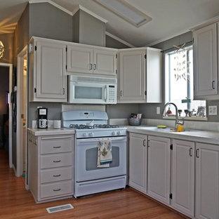 Modern inredning av ett litet kök, med en undermonterad diskho, luckor med upphöjd panel, vita skåp, kaklad bänkskiva, vitt stänkskydd, stänkskydd i porslinskakel, vita vitvaror och mellanmörkt trägolv