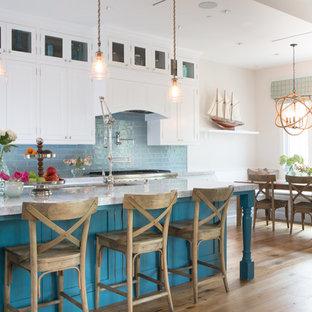 ロサンゼルスのビーチスタイルのおしゃれなキッチン (アンダーカウンターシンク、シェーカースタイル扉のキャビネット、白いキャビネット、青いキッチンパネル、サブウェイタイルのキッチンパネル、シルバーの調理設備の、無垢フローリング) の写真