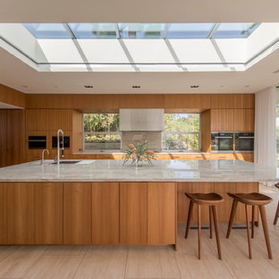 Photo of a midcentury kitchen in Los Angeles with an undermount sink, flat-panel cabinets, medium wood cabinets, window splashback, with island, beige floor and grey benchtop.