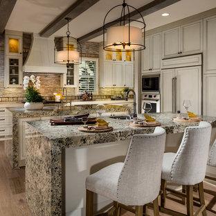 サンディエゴの大きい地中海スタイルのおしゃれなマルチアイランドキッチン (アンダーカウンターシンク、ベージュのキャビネット、御影石カウンター、マルチカラーのキッチンパネル、ボーダータイルのキッチンパネル、パネルと同色の調理設備、淡色無垢フローリング、落し込みパネル扉のキャビネット、マルチカラーのキッチンカウンター) の写真