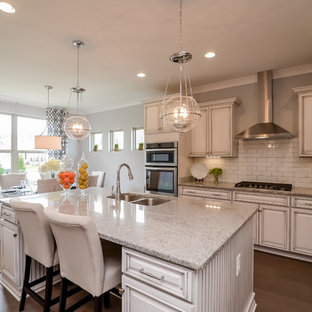 Design ideas for a mid-sized contemporary l-shaped eat-in kitchen in Nashville with a double-bowl sink, beaded inset cabinets, distressed cabinets, limestone benchtops, white splashback, subway tile splashback, stainless steel appliances, dark hardwood floors, with island and brown floor.