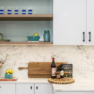ニューヨークの大きいコンテンポラリースタイルのおしゃれなキッチン (アンダーカウンターシンク、フラットパネル扉のキャビネット、白いキャビネット、大理石カウンター、マルチカラーのキッチンパネル、大理石の床、パネルと同色の調理設備、淡色無垢フローリング、ターコイズのキッチンカウンター) の写真