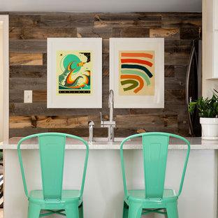 アトランタのエクレクティックスタイルのおしゃれなペニンシュラキッチン (白いキャビネット、シングルシンク、シェーカースタイル扉のキャビネット、ベージュキッチンパネル、グレーのキッチンカウンター) の写真