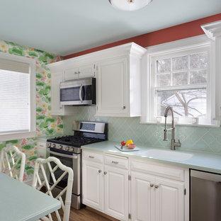 他の地域の小さいトラディショナルスタイルのおしゃれなII型キッチン (一体型シンク、レイズドパネル扉のキャビネット、白いキャビネット、人工大理石カウンター、緑のキッチンパネル、ガラスタイルのキッチンパネル、シルバーの調理設備の、クッションフロア、茶色い床、緑のキッチンカウンター) の写真