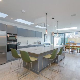 Photo of a medium sized contemporary single-wall kitchen/diner in London with a submerged sink, flat-panel cabinets, grey cabinets, quartz worktops, white splashback, stainless steel appliances, light hardwood flooring, an island, brown floors and white worktops.
