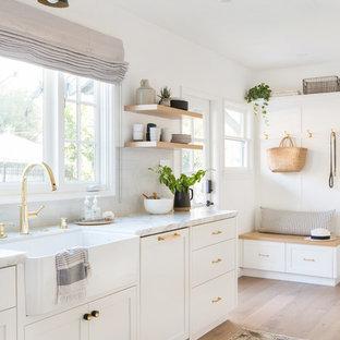 ロサンゼルスの中くらいのシャビーシック調のおしゃれなキッチン (ドロップインシンク、落し込みパネル扉のキャビネット、白いキャビネット、大理石カウンター、グレーのキッチンパネル、セラミックタイルのキッチンパネル、シルバーの調理設備、淡色無垢フローリング、アイランドなし、ベージュの床、白いキッチンカウンター) の写真
