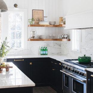 Mittelgroße Klassische Küche in L-Form mit Landhausspüle, Schrankfronten im Shaker-Stil, schwarzen Schränken, Marmor-Arbeitsplatte, Küchenrückwand in Weiß, Rückwand aus Marmor, Elektrogeräten mit Frontblende, braunem Holzboden, Kücheninsel und braunem Boden in Chicago