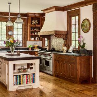 ミルウォーキーの広いヴィクトリアン調のおしゃれなキッチン (大理石カウンター、セラミックタイルのキッチンパネル、シルバーの調理設備、無垢フローリング、レイズドパネル扉のキャビネット、濃色木目調キャビネット、茶色い床) の写真