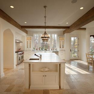 Inredning av ett klassiskt kök, med rostfria vitvaror och travertin golv