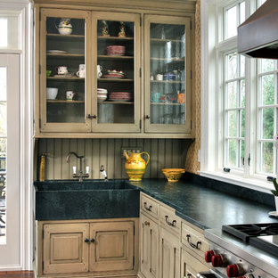 Large traditional u-shaped kitchen in Philadelphia with an integrated sink, glass-front cabinets, green cabinets, soapstone benchtops, green splashback, stainless steel appliances, medium hardwood floors and with island.