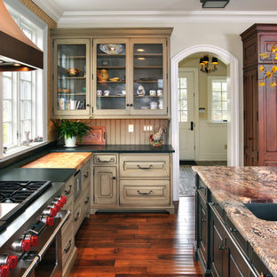 Large traditional open concept kitchen pictures - Example of a large classic u-shaped medium tone wood floor open concept kitchen design in Philadelphia with a single-bowl sink, dark wood cabinets, granite countertops, multicolored backsplash, stainless steel appliances and an island