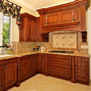 サンディエゴの大きいトラディショナルスタイルのおしゃれなキッチン (ダブルシンク、レイズドパネル扉のキャビネット、中間色木目調キャビネット、御影石カウンター、ベージュキッチンパネル、石タイルのキッチンパネル、シルバーの調理設備の、大理石の床) の写真