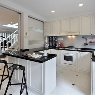 Modern kitchen designs - Inspiration for a modern white floor kitchen remodel in Singapore with a drop-in sink, white appliances and black countertops