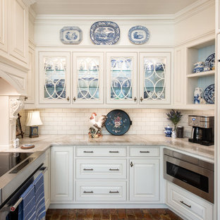Inspiration for a small classic u-shaped enclosed kitchen in Tampa with a belfast sink, beaded cabinets, white cabinets, granite worktops, white splashback, ceramic splashback, stainless steel appliances, brick flooring, red floors and white worktops.