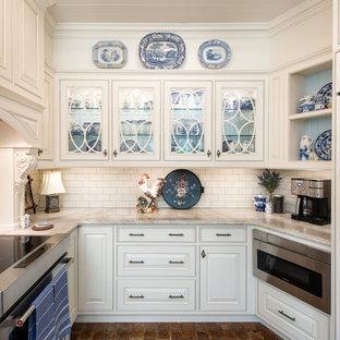 タンパの小さいトラディショナルスタイルのおしゃれなキッチン (エプロンフロントシンク、インセット扉のキャビネット、白いキャビネット、御影石カウンター、白いキッチンパネル、セラミックタイルのキッチンパネル、シルバーの調理設備、レンガの床、赤い床、白いキッチンカウンター) の写真