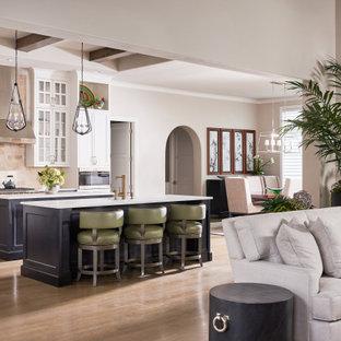 Offene Klassische Küche in L-Form mit Unterbauwaschbecken, Rückwand aus Travertin, Küchengeräten aus Edelstahl, hellem Holzboden, zwei Kücheninseln und weißer Arbeitsplatte in Dallas