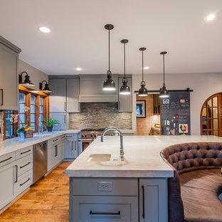Foto på ett mycket stort vintage kök, med en undermonterad diskho, skåp i shakerstil, grå skåp, stänkskydd i stenkakel, rostfria vitvaror, mellanmörkt trägolv och en köksö