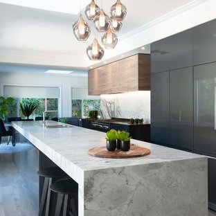 Design ideas for a large contemporary galley open plan kitchen in Sydney with a drop-in sink, marble benchtops, stone slab splashback, black appliances, with island, flat-panel cabinets, brown cabinets, grey splashback, medium hardwood floors, grey floor and grey benchtop.