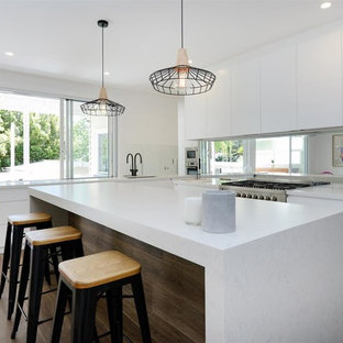 Beach style l-shaped eat-in kitchen in Sunshine Coast with an undermount sink, flat-panel cabinets, white cabinets, mirror splashback, stainless steel appliances, medium hardwood floors, with island, brown floor and white benchtop.