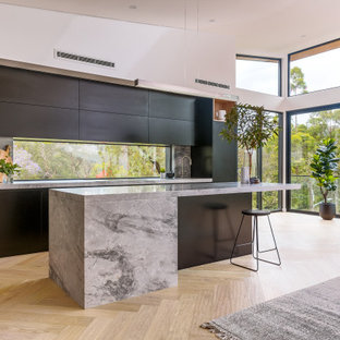 Photo of a large modern kitchen in Sydney with black cabinets, marble benchtops, marble splashback, black appliances and with island.