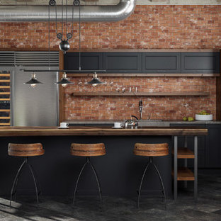 Inspiration for an industrial l-shaped open plan kitchen in Minneapolis with an integrated sink, flat-panel cabinets, black cabinets, wood benchtops, red splashback, brick splashback, stainless steel appliances, porcelain floors and with island.