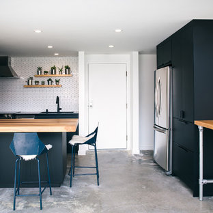 Photo of a small contemporary galley kitchen/diner in San Francisco with a submerged sink, flat-panel cabinets, black cabinets, wood worktops, white splashback, ceramic splashback, stainless steel appliances, concrete flooring, an island, grey floors and multicoloured worktops.