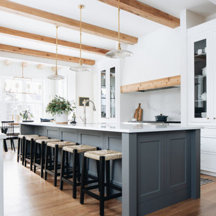 На фото: параллельная кухня в стиле кантри с обеденным столом, фасадами в стиле шейкер, белыми фасадами, белым фартуком, паркетным полом среднего тона, островом, коричневым полом, белой столешницей и балками на потолке с