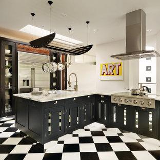 Пример оригинального дизайна: отдельная кухня в современном стиле с врезной раковиной, черными фасадами, техникой из нержавеющей стали, полом из линолеума и полуостровом