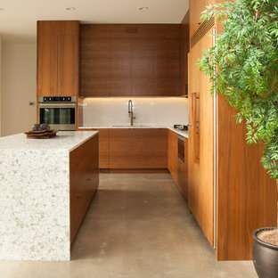 Inspiration for a mid-sized modern l-shaped concrete floor eat-in kitchen remodel in Portland with flat-panel cabinets, medium tone wood cabinets, white backsplash and subway tile backsplash