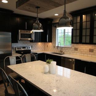 デンバーの大きいインダストリアルスタイルのおしゃれなキッチン (アンダーカウンターシンク、シェーカースタイル扉のキャビネット、濃色木目調キャビネット、クオーツストーンカウンター、白いキッチンパネル、サブウェイタイルのキッチンパネル、シルバーの調理設備の、スレートの床) の写真