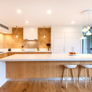 Inspiration for a large contemporary l-shaped open plan kitchen in Adelaide with light wood cabinets, solid surface benchtops, medium hardwood floors, with island, a double-bowl sink, flat-panel cabinets, brown splashback and black appliances.