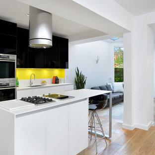 トロントのモダンスタイルのおしゃれなキッチン (アンダーカウンターシンク、フラットパネル扉のキャビネット、黒いキャビネット、黄色いキッチンパネル、珪岩カウンター、シルバーの調理設備の、淡色無垢フローリング) の写真